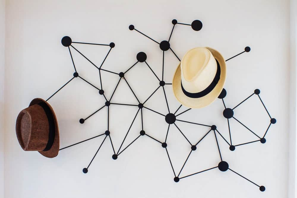 A decorative and artistic hat rack mounted on a white wall.