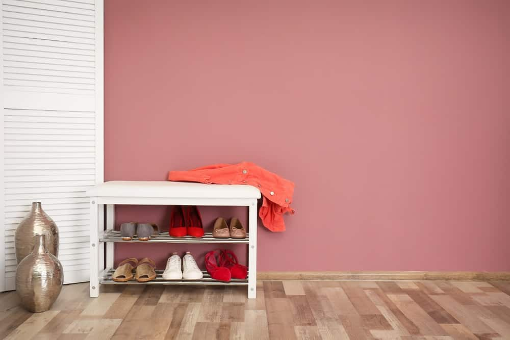 A foyer with pink walls and a white small bench built with a shoe rack.