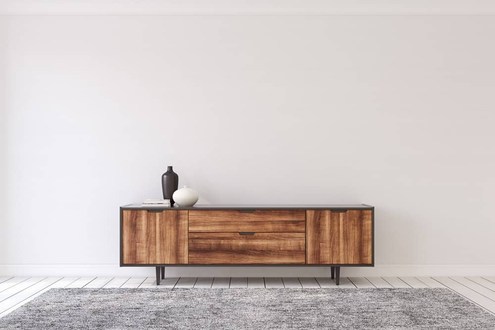 A simple foyer with a low wooden cabinet that also functions as a console table.