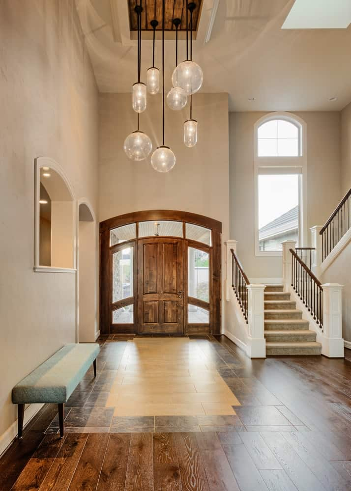 A grand foyer with a tall ceiling and a bench on the side.