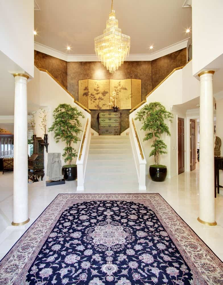A grand foyer with a symmetry of two pillars, two potted plants and a large area rug in the middle.