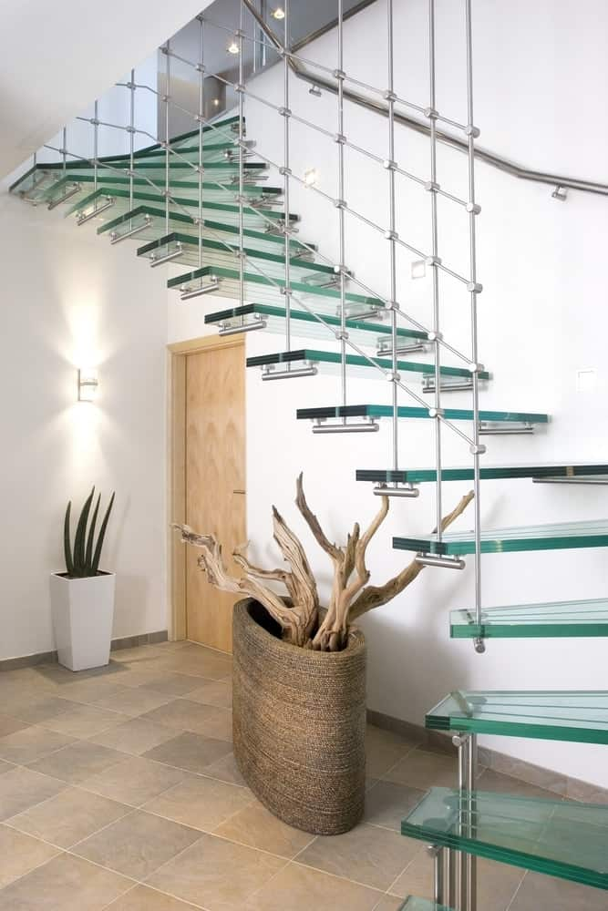 A simple foyer under the glass stairs with a two different decorations on either side of the wooden door.