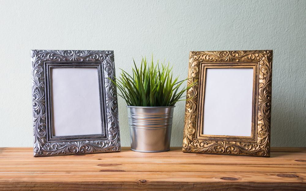 A silver frame and a golden frame on a wooden surface.
