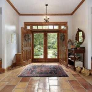 A luxurious foyer with terracotta tiles and a patterned area rug.