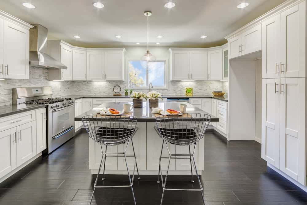 A luxurious kitchen with dark flooring tiles and white shaker cabinets.