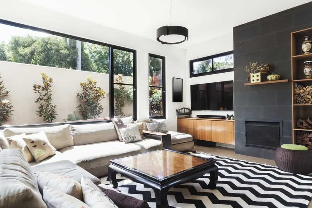 Monochrome living room with wood and grey tiling accents and chevron pattern rug.