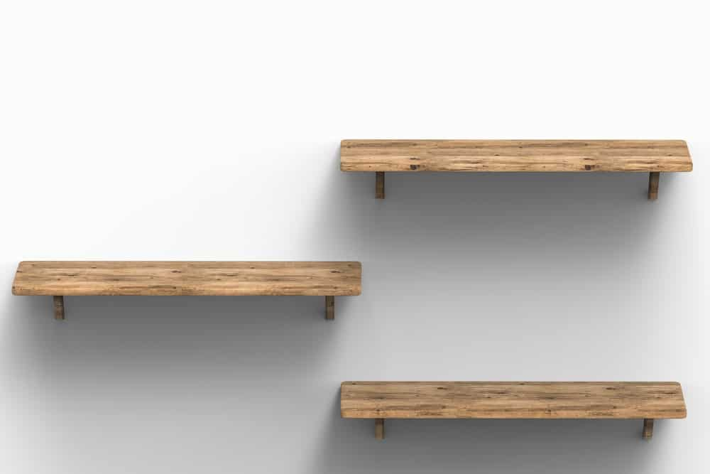 Three wooden floating shelves on a white wall.