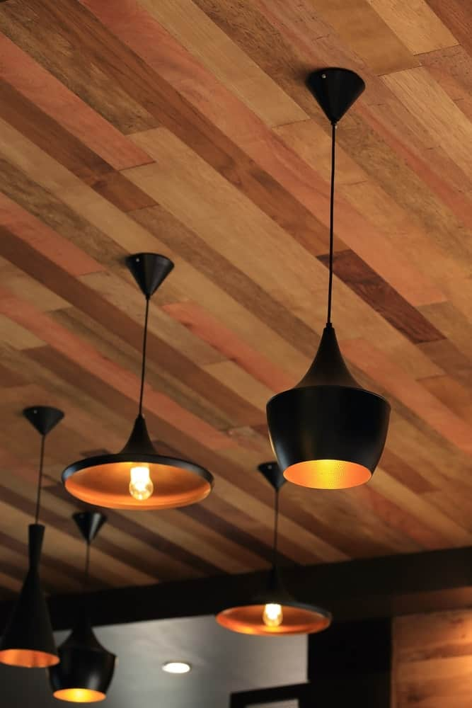Black hanging pendant lights from the wood-paneled ceiling.