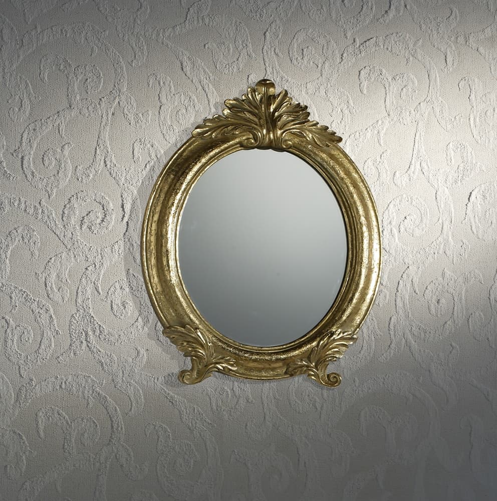 A gold framed elliptical mirror mounted on a white textured wall.