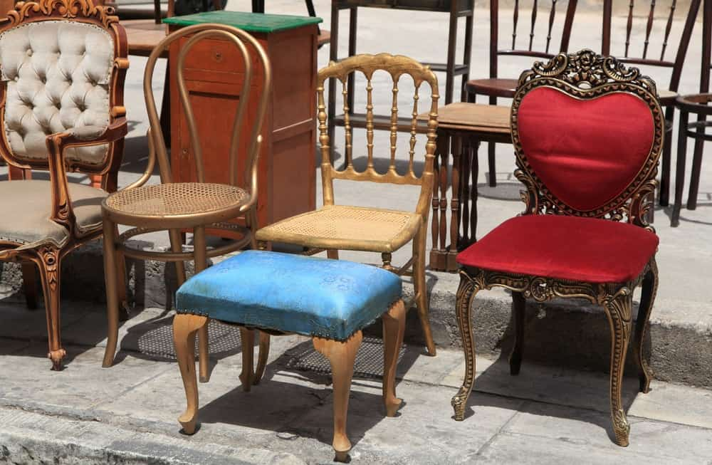 A set of different chairs on display at the pavement.