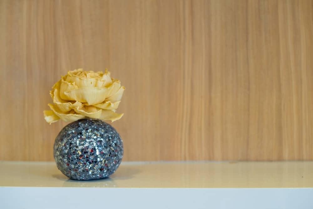 A decorative setup of a golden paper rose in a glittery vase.