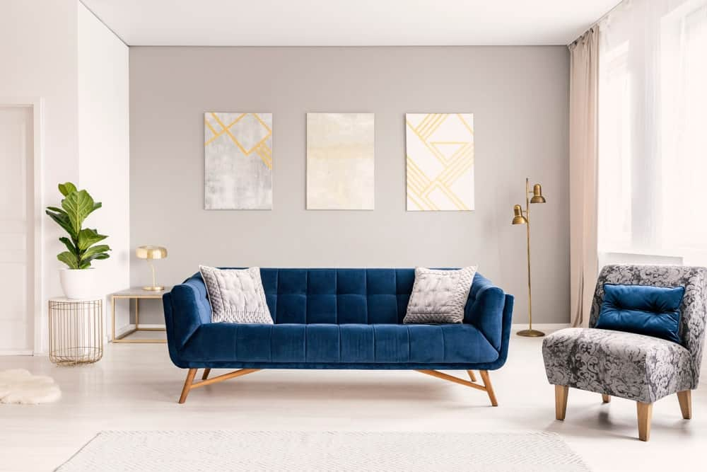A bright living room with neutral tones that make the blue green velvet couch and pillow stand out.