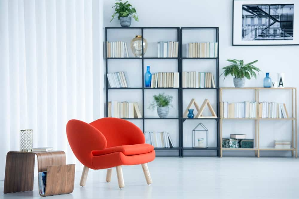 A simple Industrial-style living room complemented by its bookshelves against the white wall.