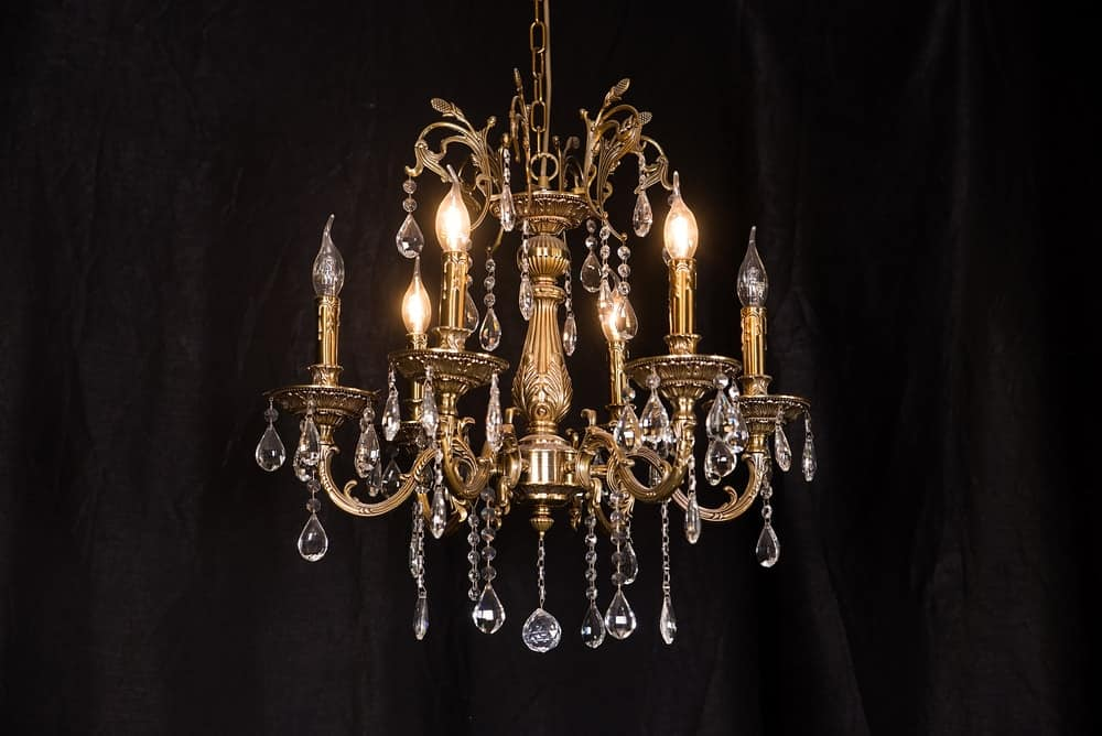 A close-up of a majestic chandelier with crystals and yellow light.