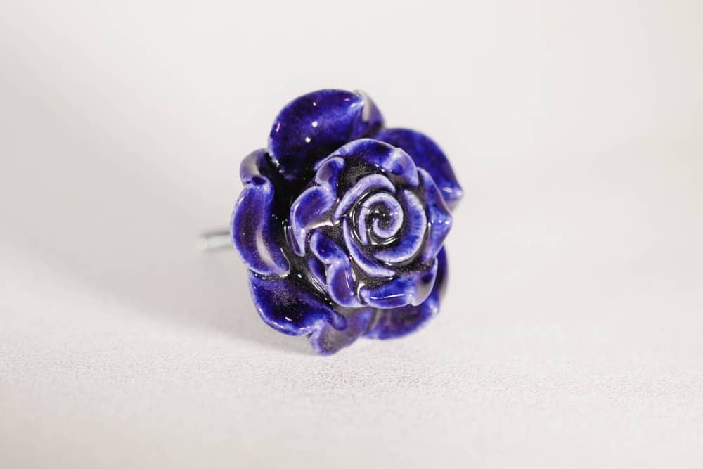 A close-up of a blue ceramic drawer handle in the shape of a rose.