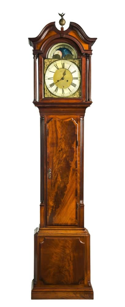 A wooden varnished grandfather clock on a white background.
