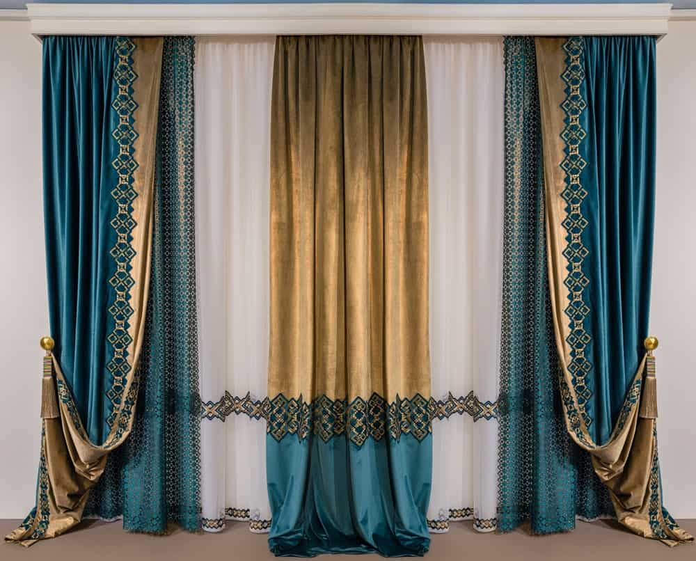 A set of beautiful green and gold patterned curtains.