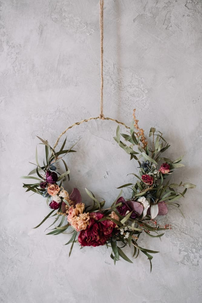 A set of dried flowers arranged on a circular decorative hanging ornament.