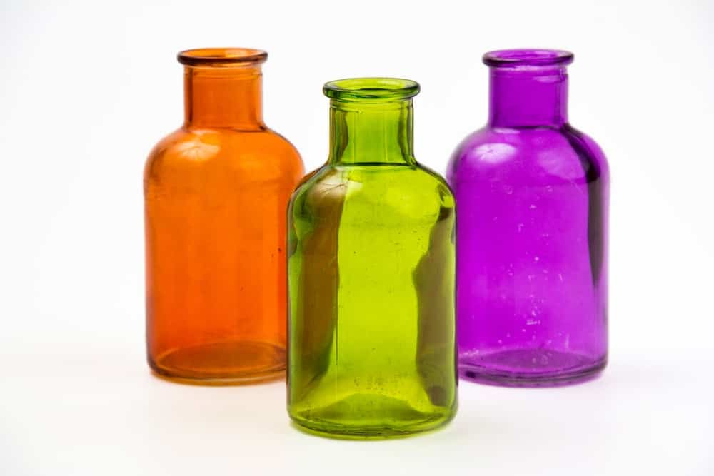 A set of three colorful decorative glass bottles.