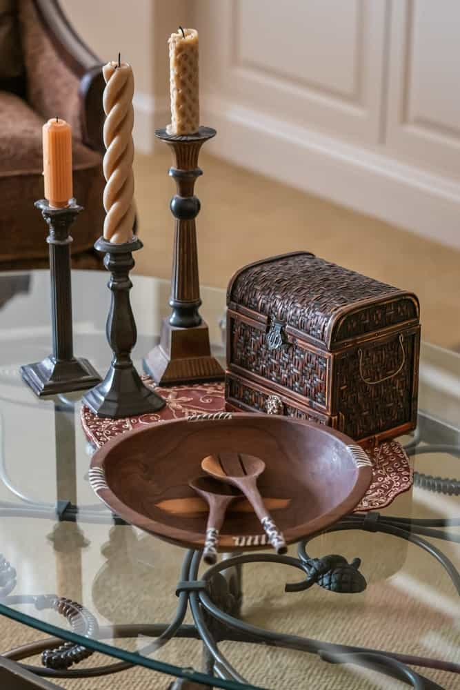 A glass coffee table decorated with candlesticks, a wooden chest and a wooden plate.