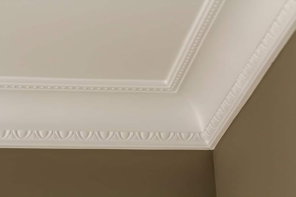 A close-up of crown molding in between the gray walls and white ceiling.