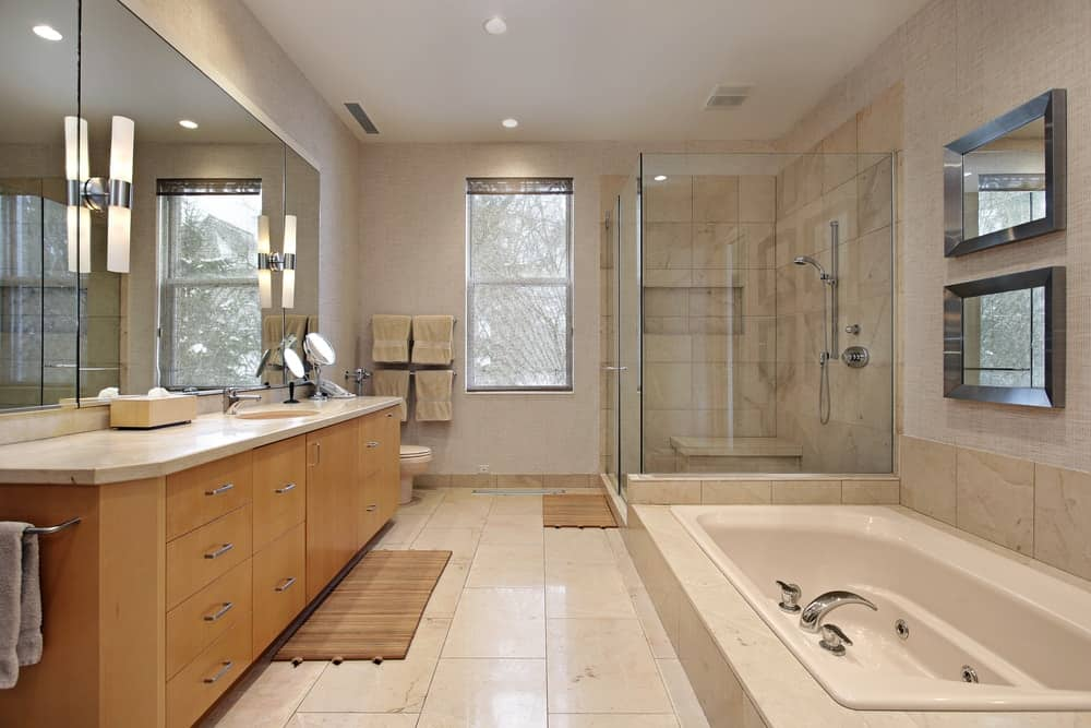 A luxurious master bathroom with a large mirror across from the bathtub.