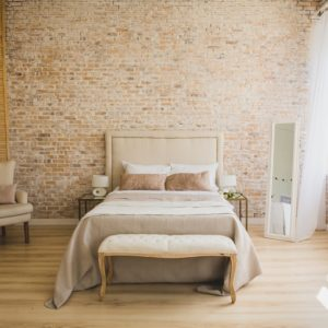 A lovely master bedroom with brick walls and ample natural lighting.