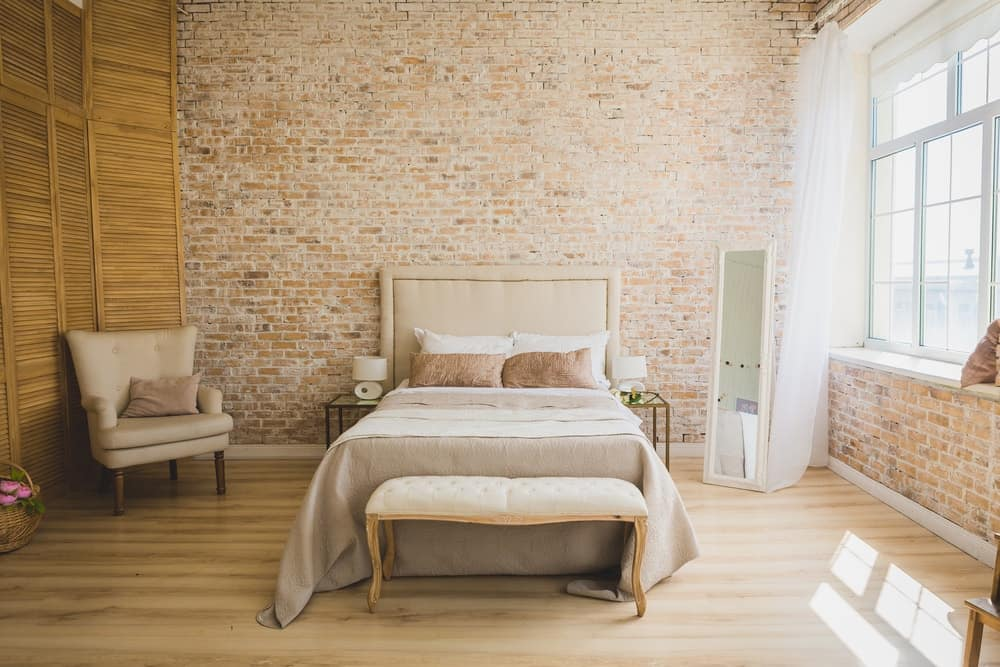 A lovely primary bedroom with brick walls and ample natural lighting.
