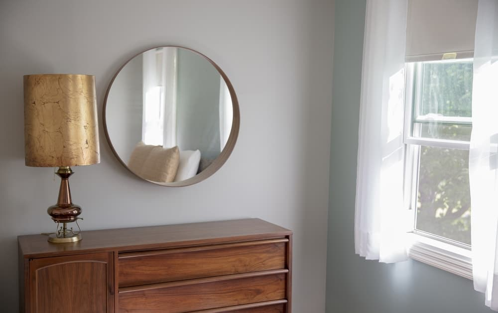 A close look at the bedroom corner with a round mirror mounted above the wooden dresser.
