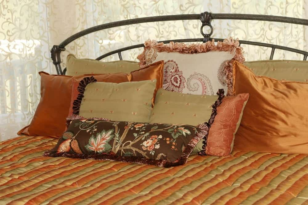 A close look at the bed that has a patterned bed sheet and a collection of pillows.