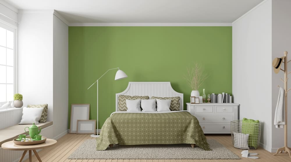 A charming master bedroom with a large avocado green wall behind the headboard.
