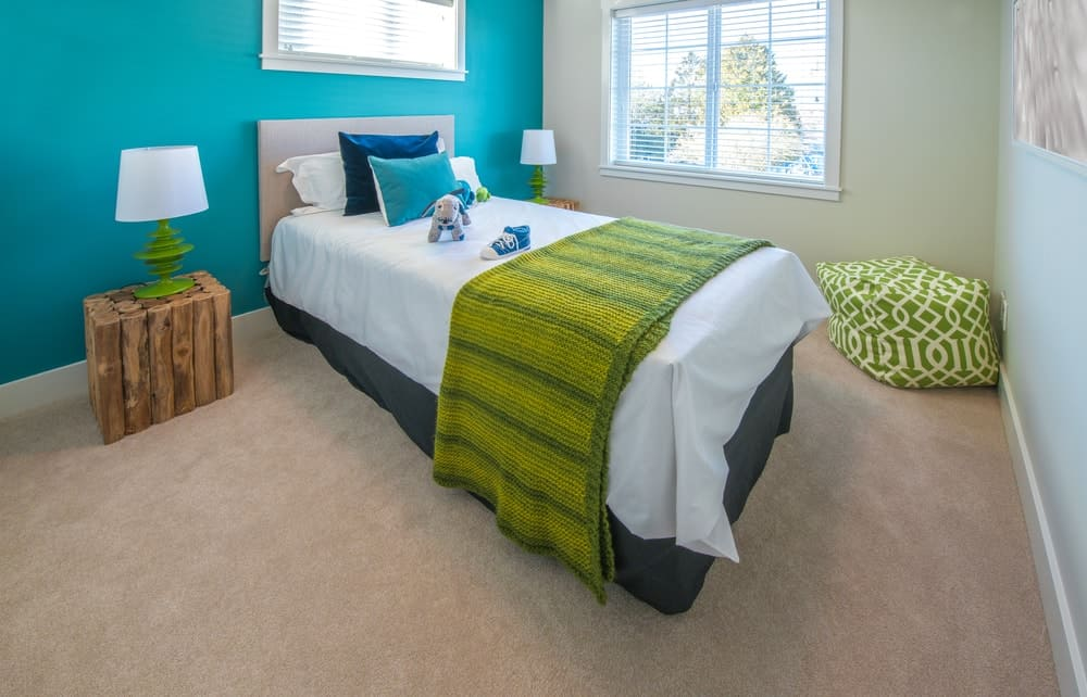 A charming bedroom complemented by its varying shades of green and blue.