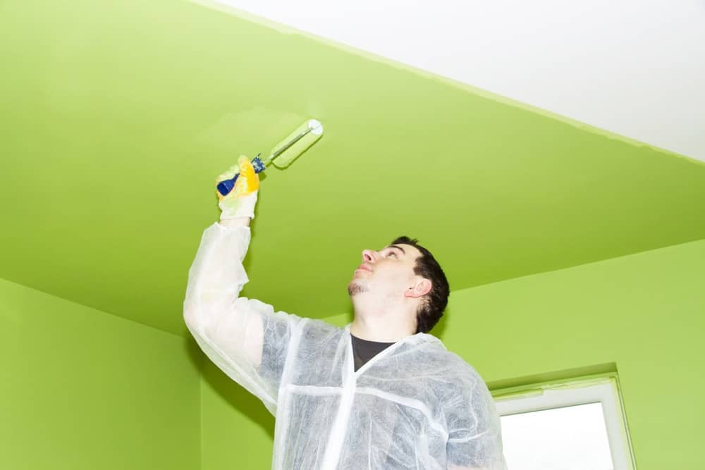 A man painting the ceiling with an avocado green paint using a roller.