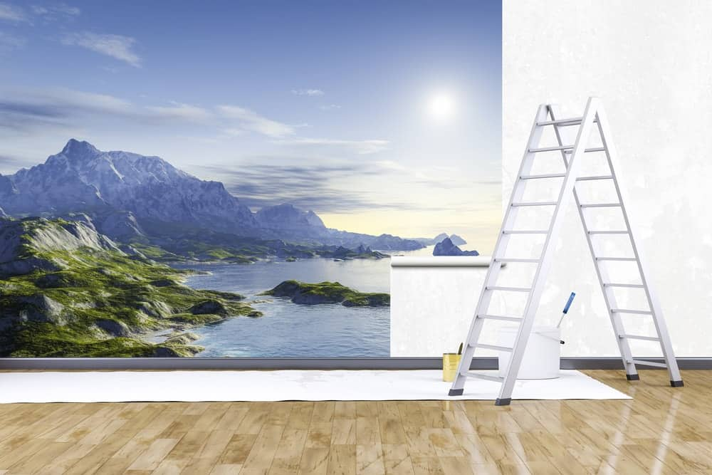 A large mural of a seaside scene being installed on a white wall.