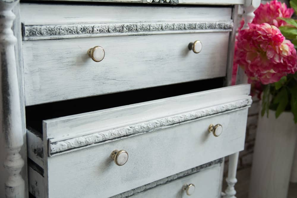 A close-up of a shabby-chic dresser with a light gray tone.