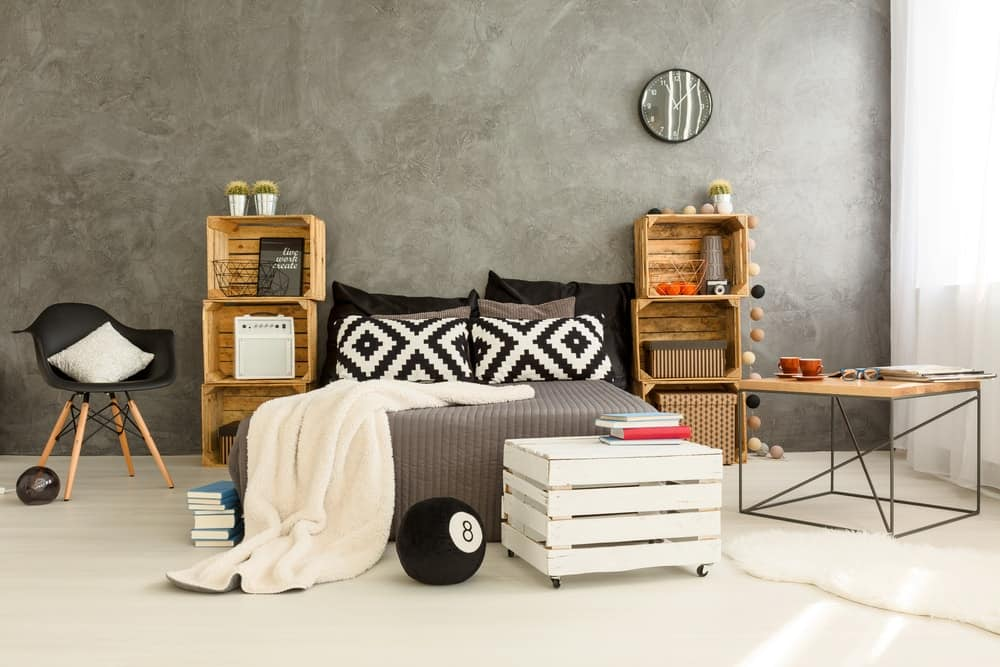 A lovely bedroom with crate boxes on each side of the bed to serve as bedside tables to match the crate box chair at the foot of the bed.