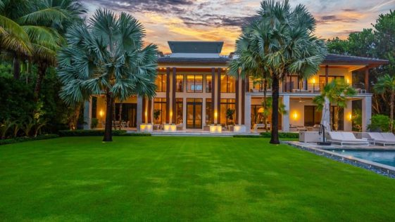 A beautiful mansion with wide glass walls and tall columns complemented by warm yellow lights glowing from the interiors as well as a couple of tall tropical trees. Images courtesy of Toptenrealestatedeals.com.