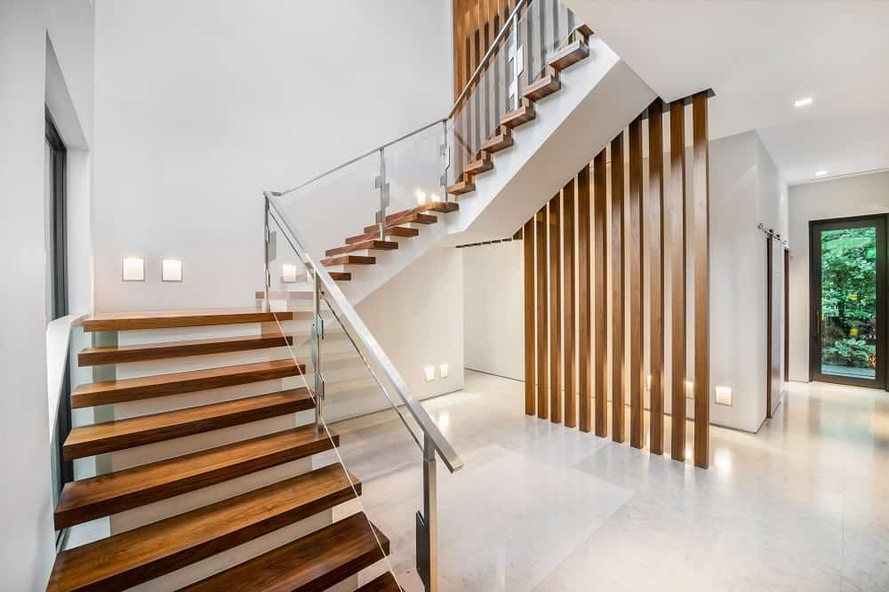 The bright interior of the house due to the bright flooring and walls are balanced by the wooden details of the stairs as well as a decorative divider under the stairs. Images courtesy of Toptenrealestatedeals.com.