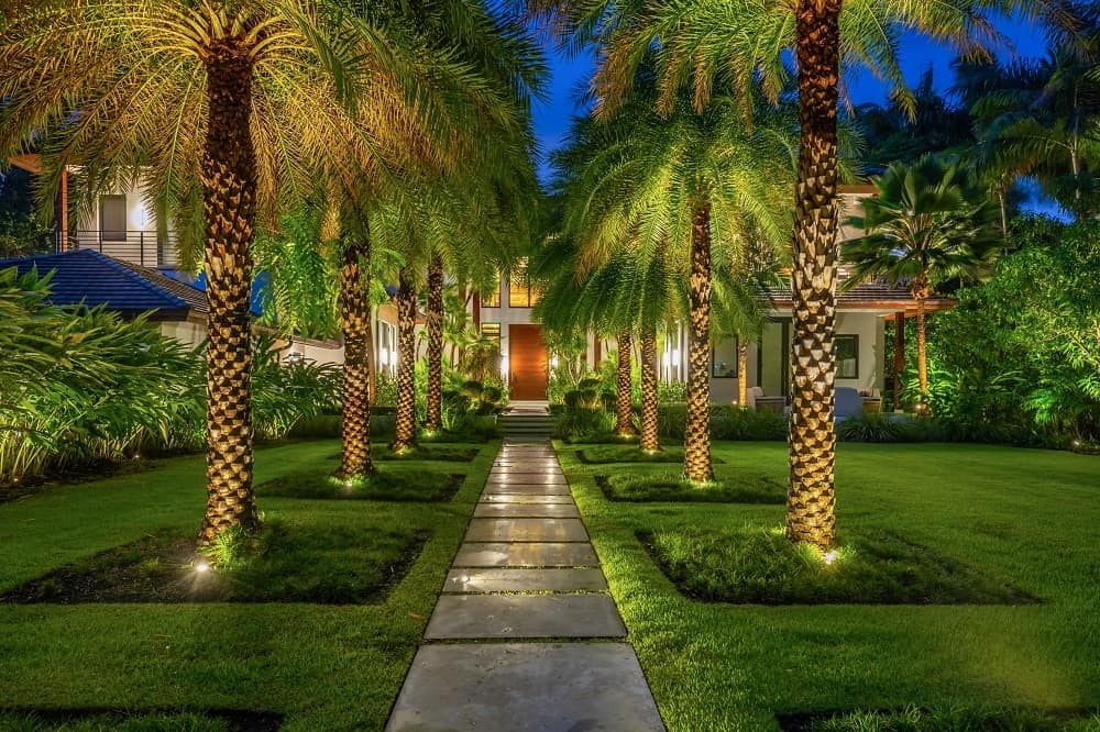 The lavish front yard of this mansion has a central walkway complemented by the flanking tall tropical trees lined on both sides and brightened by spot lights for an ethereal look. Images courtesy of Toptenrealestatedeals.com.