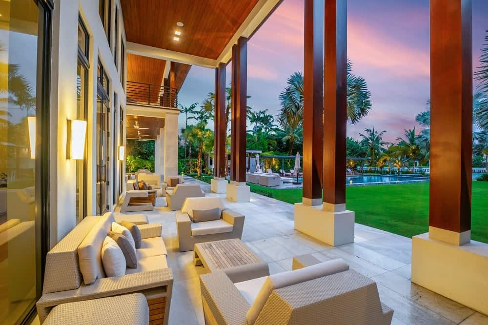 The patio at the back of the house has sets of outdoor sofas and arm chairs under soaring wooden ceilings with a view of the lush landscaping of the backyard. Images courtesy of Toptenrealestatedeals.com.