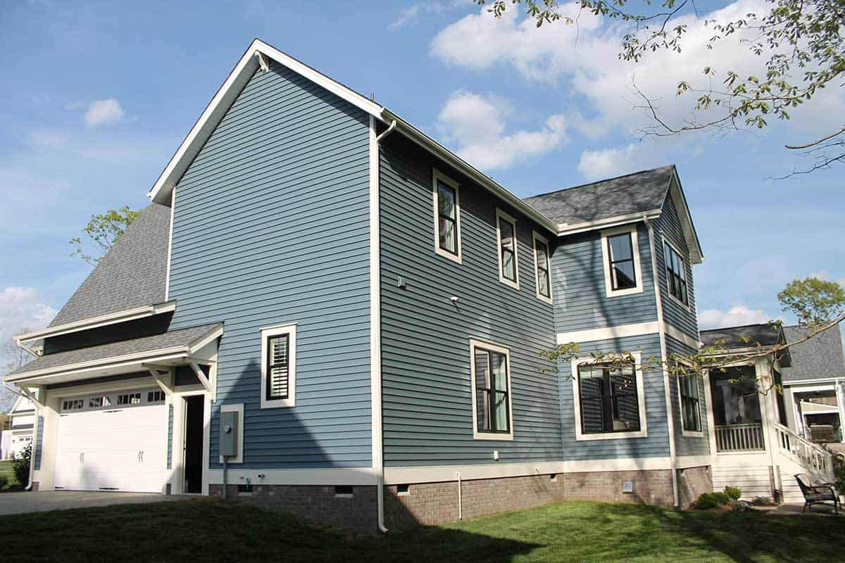 Side exterior of the house showing the 2 car garage and blue siding fitted with plenty of aluminum framed windows.