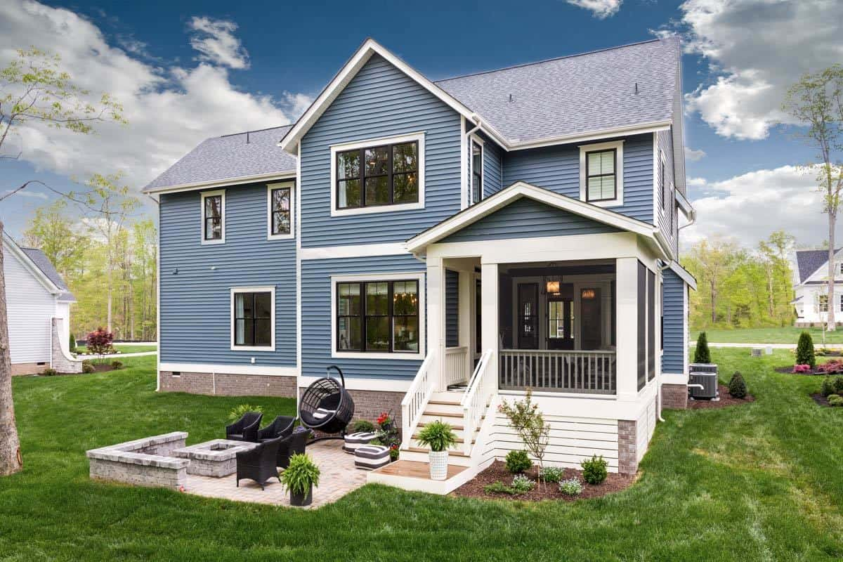 The rear exterior view features a large screened porch and an open patio filled with various cozy seats.
