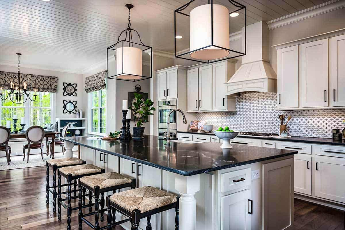 The kitchen boasts white cabinetry and a black marble top island paired with wooden barstools.