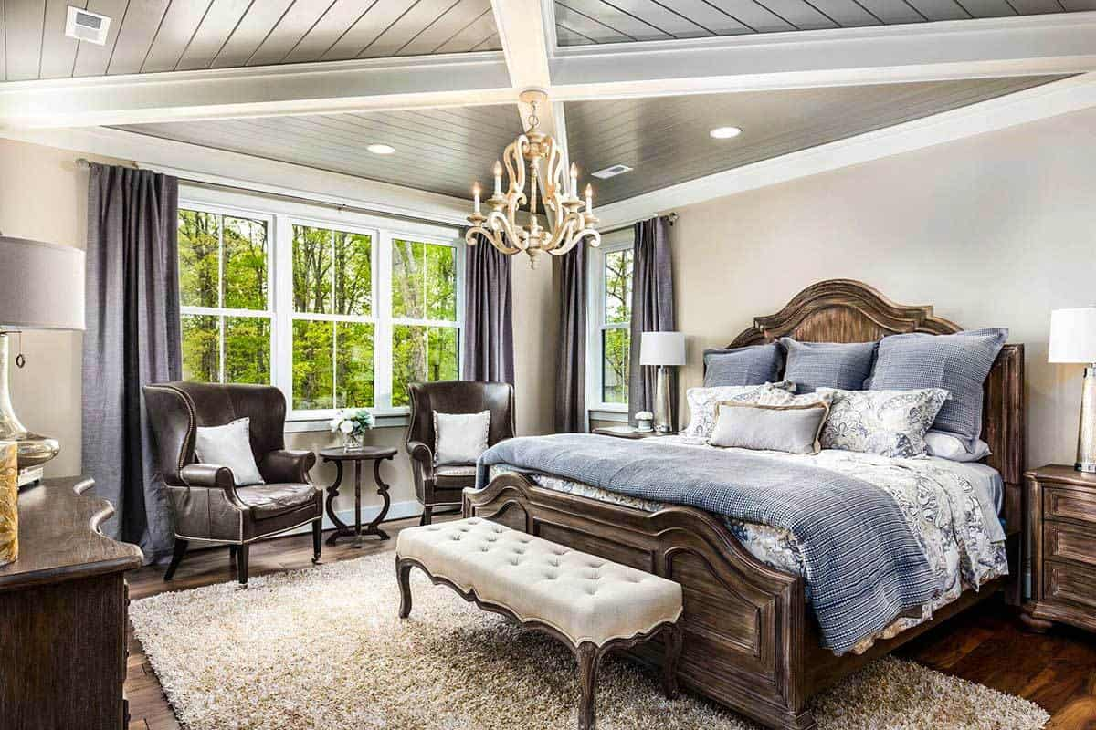 The primary bedroom offers leather wingback chairs and a cozy wooden bed well lit by a lovely candle chandelier.