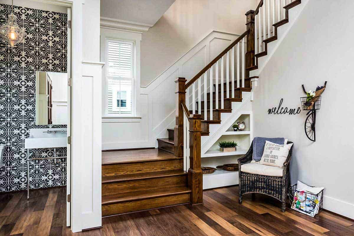 Under the staircase are built-in shelves and a wicker chair topped with cushion and pillow. On its left side is the bathroom accented with decorative patterned tiles.
