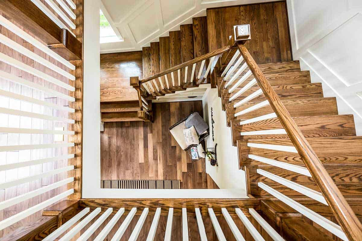 A top view of the winding staircase with rich wooden treads and matching handrails.