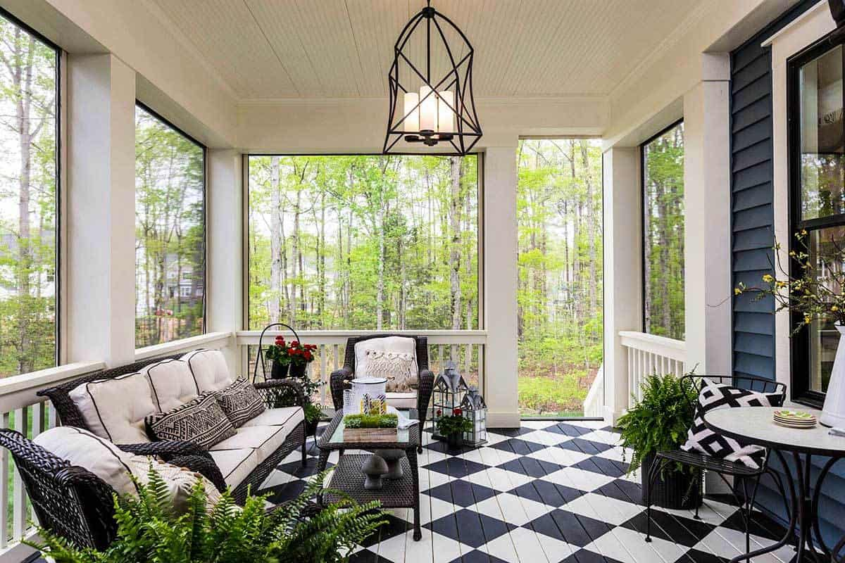 The screened porch showcases a wrought iron pendant and cushioned wicker seats over the checkered flooring.