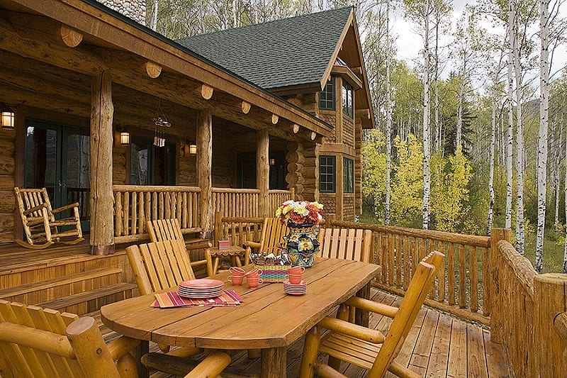Home's deck with a rustic table and plenty of wooden chairs blending in with the wide plank flooring and railings.