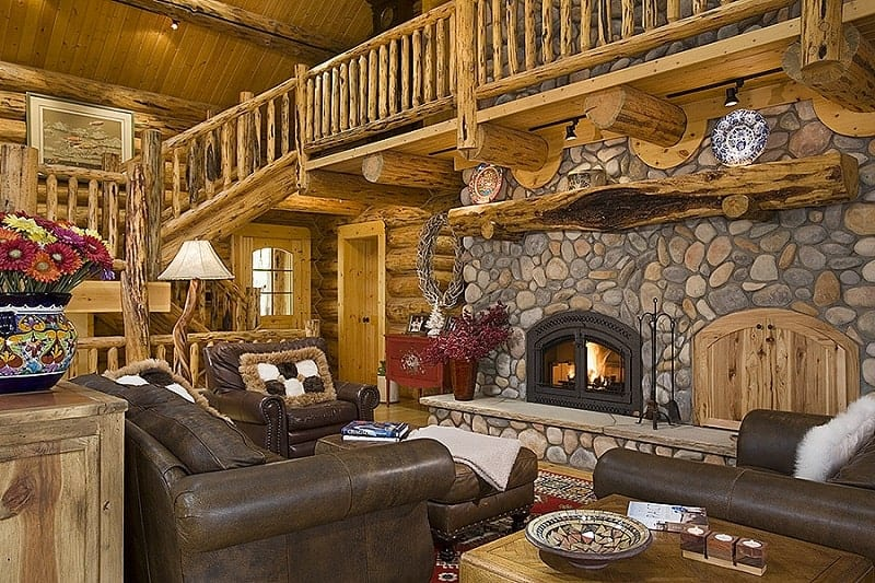 The great room with a gorgeous stone fireplace and brown leather sofas paired with a matching ottoman.