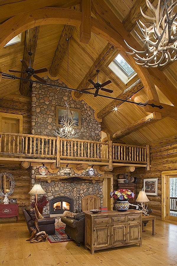 This view of the great room shows the high cathedral ceiling with exposed beams and hanging driftwood chandeliers.